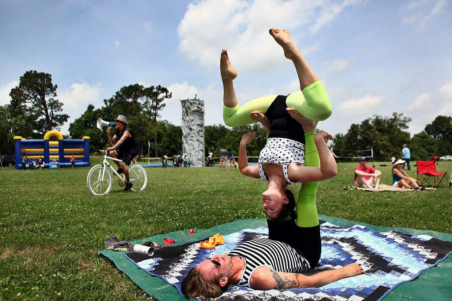 Stephanie Peck, top, and Derek Gloden perform acroyoga for visitors to Overton Park for the second day of Merrymaking festival in Memphis, Tenn., Saturday, June 7, 2014. Photo: Kyle Kurlick, Associated Press