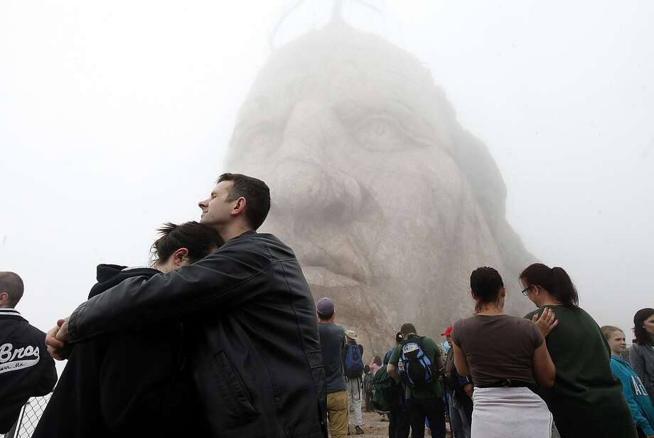 Paul and Lydia Block, of Rapid City, S.D., embrace after reaching the top of Crazy Horse Memorial near Custer, S.D., in thick fog Saturday morning, June 7, 2014, during the annual Volksmarch. Photo: Chris Huber, Associated Press