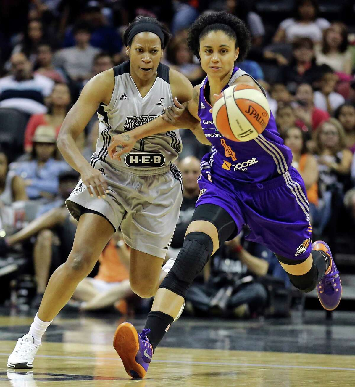 San Antonio Stars' Jia Perkins and Phoenix Mercury's Candice Dupree chase after a loose ball during their WNBA game Saturday June 7, 2014 at the AT&T Center. The Mercury won in double overtime 91-79.