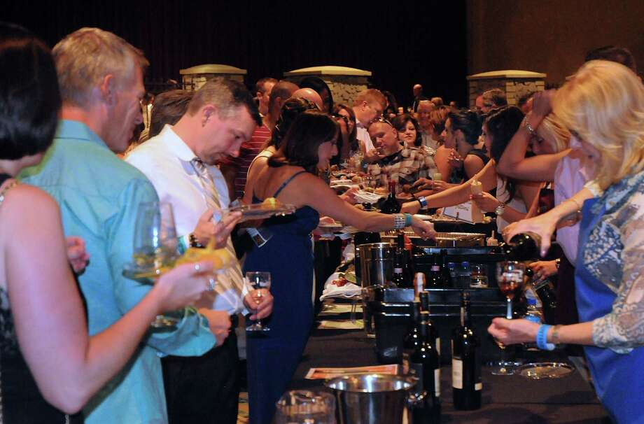 Guests line up at a sampling table to try the wine and food samples during the Wine Rendezvous Grand Tasting, a part of Wine Week, at The Woodlands Waterway Marriott.  Photo: David Hopper, For The Chronicle / freelance