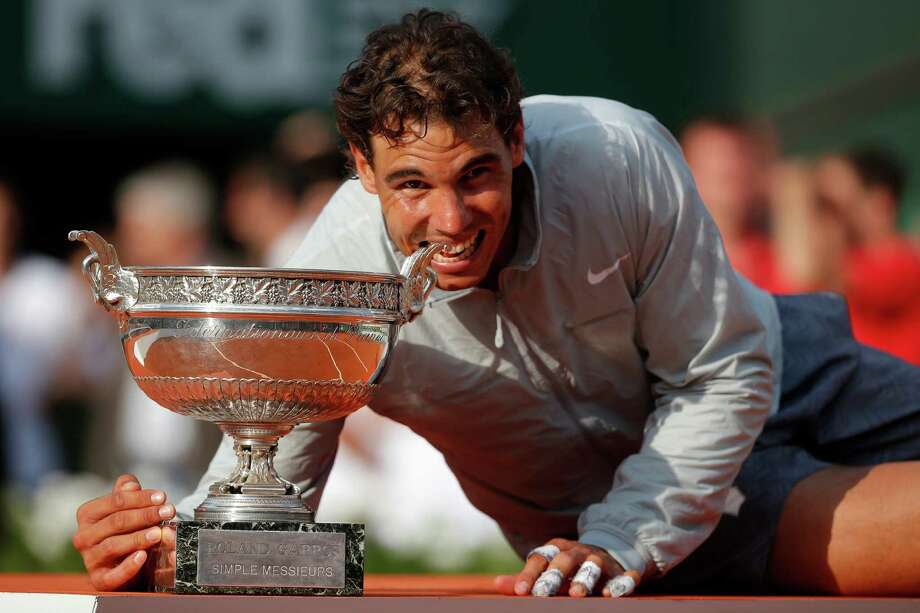 Spain's Rafael Nadal bites the trophy after winning the final of the French Open tennis tournament against Serbia's Novak Djokovic at the Roland Garros stadium, in Paris, France, Sunday, June 8, 2014. Nadal won in four sets 3-6, 7-5, 6-2, 6-4. (AP Photo/Michel Euler) Photo: Michel Euler, Associated Press / AP