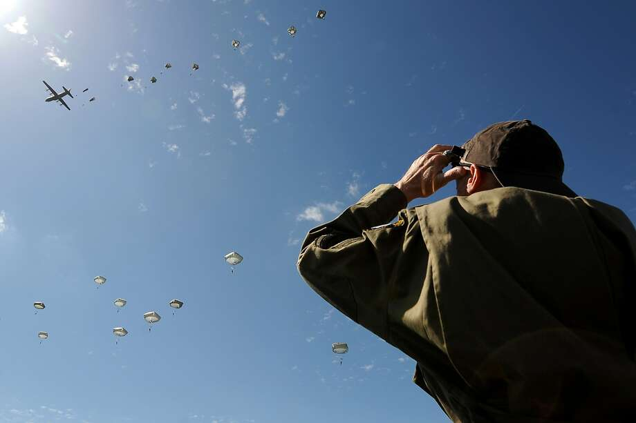 A spectator watches paratroopers jumping from a plane in Sainte-Mere-Eglise, northern France, during a commemoration of the 70th anniversary of D-Day. Photo: Jean-sebastien Evrard, AFP/Getty Images