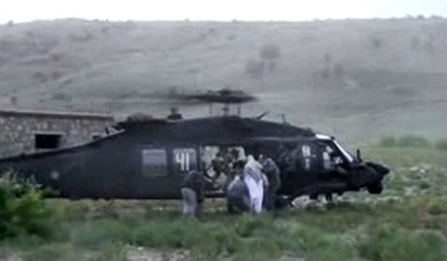 FILE - This image taken from video obtained from Voice Of Jihad Website, authenticated based on its contents and other AP reporting, shows men in civilian clothing leading Sgt. Bowe Bergdahl, in white, towards a helicopter in eastern Afghanistan.  Bergdahl was freed on May 31, 2014, in exchange for five Afghan detainees held in the U.S. prison at Guantanamo Bay, Cuba. Two American values, never leave a man behind and never negotiate with terrorists, collided in the Bergdahl calamity. Each ethos runs deep in the American conscience, yet has been violated through history and notably in the age of terrorism, where traditional standards of warfare, spying and negotiating are run through a hall of mirrors. (AP Photo/Voice Of Jihad Website via AP video) Photo: Uncredited, Associated Press