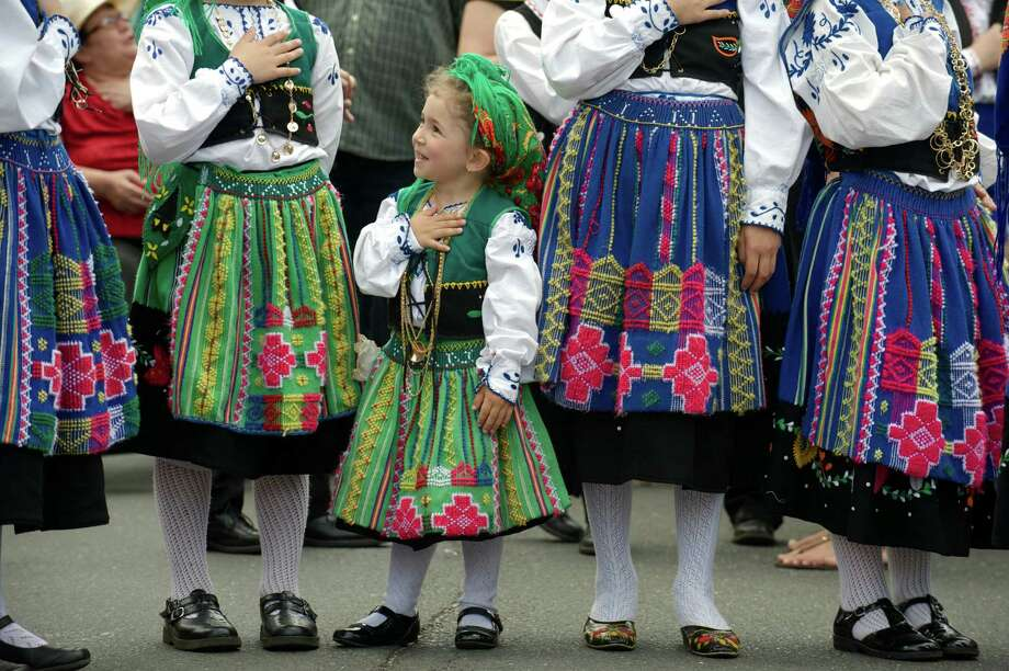 Sophia Lopes, 4, of Danbury, checks the other girls to see if she is holding her hand correctly during the National Anthem while marching in the annual Portuguese Day Parade in Danbury, Conn, on Sunday, June 8, 2014. The girls are from Escola Manuel Cipriano, the Manuel Cipriano School, which is part of the Immaculate Heart of Mary Church in Danbury. Photo: H John Voorhees III / The News-Times Freelance
