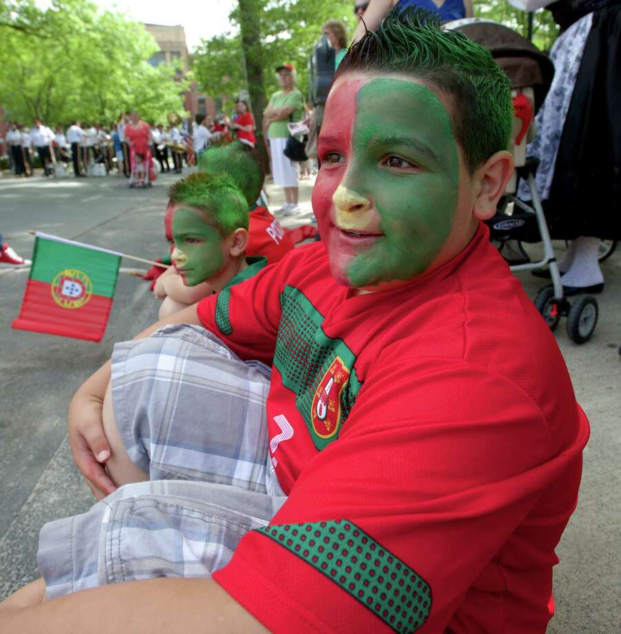 Gabriel Sousa, 11, of Danbury, watches the annual Portuguese Day Parade in Danbury, Conn, on Sunday, June 8, 2014. Sousa said he normally paints his hair green & red for the parade but he wanted to do more this year, so he painted his face as well. Photo: H John Voorhees III / The News-Times Freelance