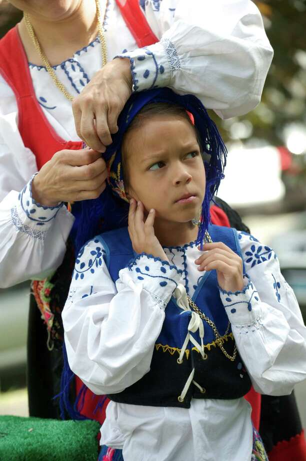 Isabella Garcia, 7, of New Fairfield, has her head garment put on by her mom, Isabel Garcia, 39, before the start of the annual Portuguese Day Parade in Danbury, Conn, on Sunday, June 8, 2014. Photo: H John Voorhees III / The News-Times Freelance