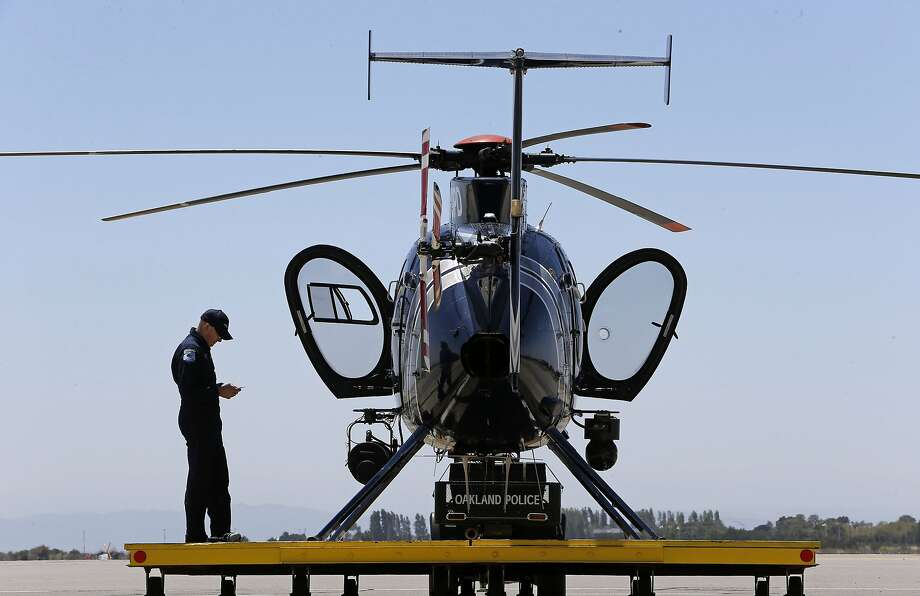 Oakland Police Department pilot Sean McClure does a safety check on the helicopter at its base at North Field in the city. The department wants to increase the helicopter's patrols from eight to 16 hours per week. Photo: Michael Macor, The Chronicle