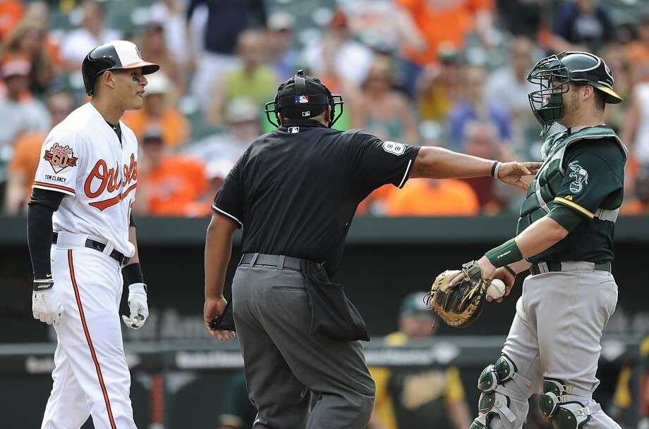 Umpire Adrian Johnson restrains the A's Stephen Vogt after Baltimore's Manny Machado lost his grip on his bat. Photo: Gail Burton, Associated Press