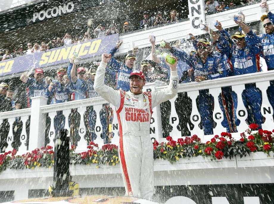 Dale Earnhardt Jr. is at the center of the cele- bration after his second Sprint Cup win this season. Photo: Mike Groll, Associated Press