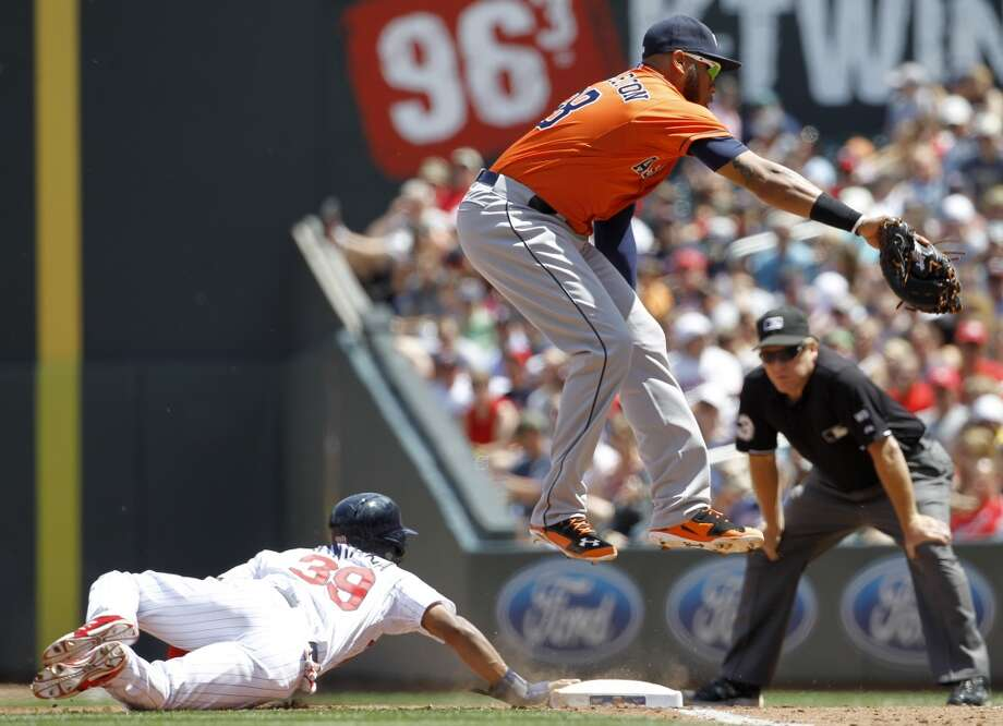 Astros first baseman Jon Singleton leaps for the throw from pitcher Collin McHugh. Photo: Ann Heisenfelt, Associated Press