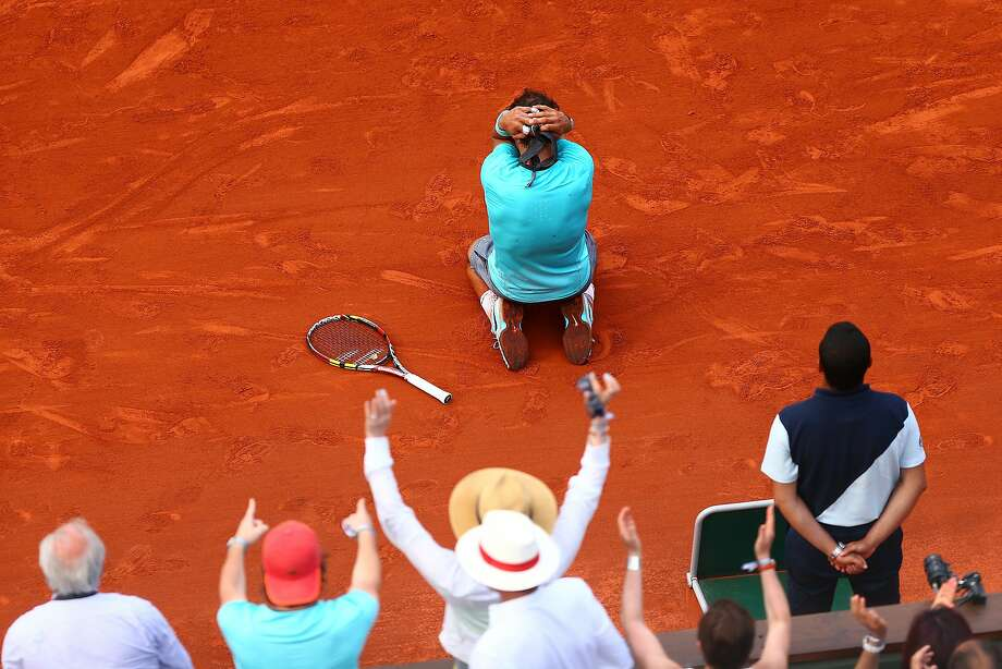 Rafael Nadal is brought to his knees, above, by the realization of his ninth French Open title. Photo: Dan Istitene, Getty Images