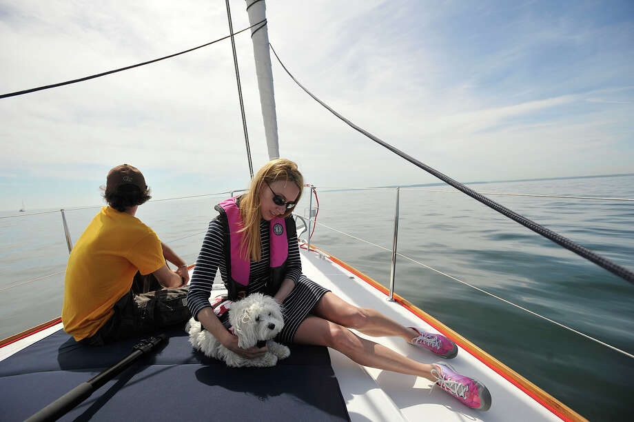 Joseph Spinella and Stacey Daveluy, with her dog Lucy, lounge on the front of the VIP boat before the start of the 29th annual Mayor's Cup Race on the Long Island Sound off shore from Stamford, Conn., on Sunday, June 8, 2014. The sailboat regatta was later cancelled due to a lack of wind. Photo: Jason Rearick / Stamford Advocate