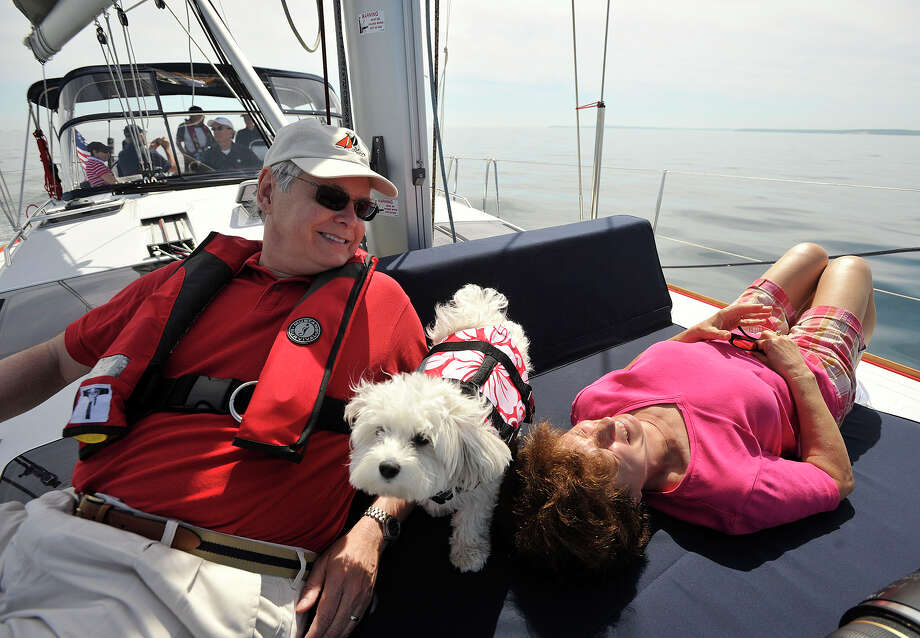 Mayor David Martin lounges with his wife, Judy, and the captain's dog, Lucy, while aboard the VIP boat before the start of the 29th annual Mayor's Cup Race on the Long Island Sound off shore from Stamford, Conn., on Sunday, June 8, 2014. The sailboat regatta was later cancelled due to a lack of wind. Photo: Jason Rearick / Stamford Advocate
