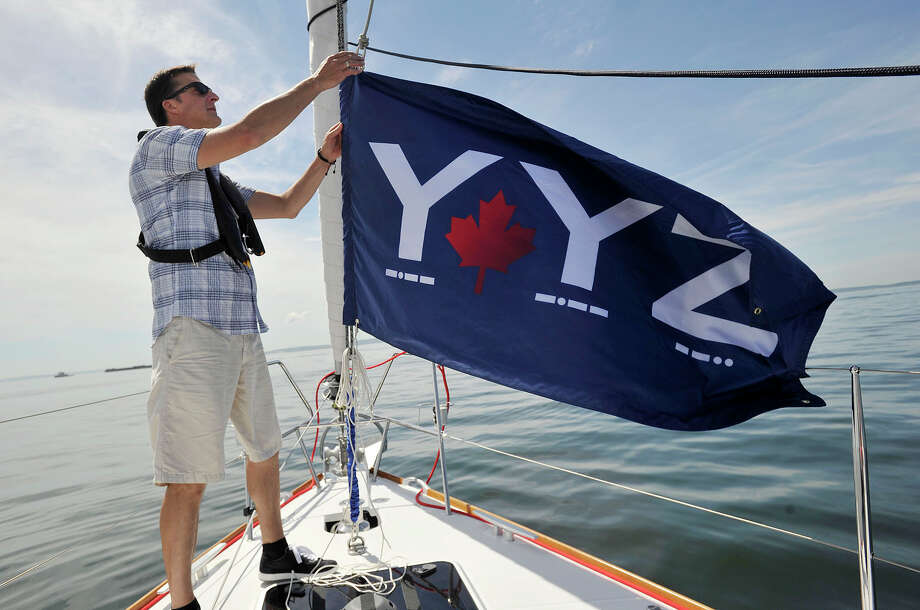 Captain Justin Bonar brings down his boat's flag to avoid confusion with another boat from aboard the VIP boat before the start of the 29th annual Mayor's Cup Race on the Long Island Sound off shore from Stamford, Conn., on Sunday, June 8, 2014. The sailboat regatta was later cancelled due to a lack of wind. Photo: Jason Rearick / Stamford Advocate