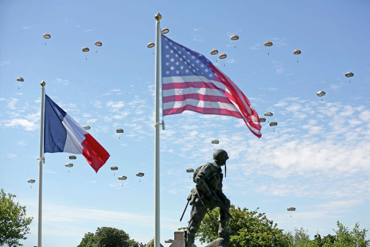 Paratroopers are dropped near the Normandy village of Sainte Mere Eglise, western France, during a mass air drop, Sunday June 8, 2014, as part of commemorations of the 70 anniversary of the D-Day landing. World leaders and veterans gathered by the beaches of Normandy on Friday to mark the 70th anniversary of the World War II D-Day landings. Visible at foreground is bronze sculpture Iron Mike, a monument dedicated to the American airborne soldiers who fought on the D Day.
