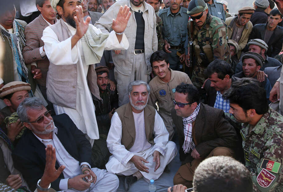 Afghan presidential candidate Abdullah Abdullah, center, sits as he listens to Afghans during a visit of a flood affected area in the Guzirga i-Nur district of Baghlan province, Afghanistan, Sunday, June 8, 2014. More than 80 bodies have been found after a devastating flash flood in Afghanistan's mountainous and remote north, a provincial official said Sunday, as police and villagers scoured the rugged terrain for missing people. Photo: Massoud Hossaini, AP / AP Pool