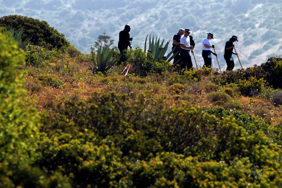 British policemen search the ground using sticks inside a cordoned-off area, in Praia da Luz, Lagos, southern Portugal, Sunday, June 8, 2014. Police began the seventh day of the investigation into the disappearance of Madeleine McCann searching a cordoned off area of scrubland near where the British girl vanished seven years ago. Photo: Francisco Seco, AP / AP