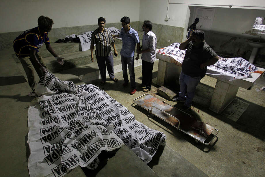 Volunteers look at dead bodies of people killed during an attack by unknown gunmen on Jinnah International Airport, Sunday night, June 8, 2014, in Karachi, Pakistan. Gunmen disguised as police guards stormed an airport terminal used for VIPs and cargo in Pakistan's largest city Sunday night, killing at least nine people as explosions echoed into the night, officials said. Photo: Fareed Khan, AP / AP