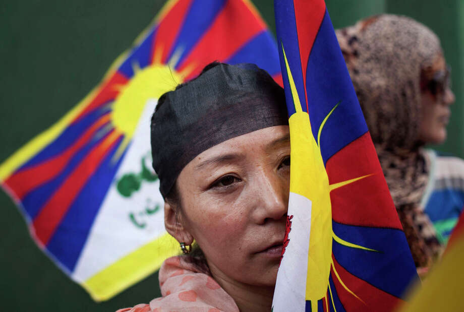 An Exile Tibetan woman holding a Tibetan flag listens to a speaker as they protest against the visit of Chinese Foreign Minister Wang Yi in New Delhi, India, Sunday, June 8, 2014. Wang Yi is visiting India's new leaders in hopes of spurring stalled trade and easing decades of tensions between the Asian nations. The protestors also urged Indian Prime Minister Narendra Modi to raise the Tibet issue with Wang. Photo: Tsering Topgyal, AP / AP