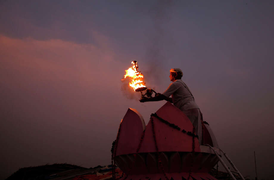 A Indian Hindu priests rotate traditional lamps in circular movements as they perform evening prayers at Sangam, the confluence of the Rivers Ganges, Yamuna and the mythical Saraswati, on the occasion of Ganga Dussehra festival in Allahabad, India, Sunday, June 8, 2014. Hindus across the country celebrate Ganga Dussehra by worshiping the River Ganges, which is considered as the most sacred and the holiest river. The water of the Ganges is worshiped in sealed containers in every home, sprinkled as a benediction of peace. Photo: Rajesh Kumar Singh, AP / AP