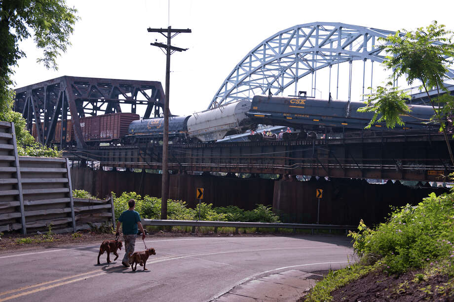 Train cars hang off the side of a railroad bridge at the site of a train derailment in McKeesport, Pa., on Sunday, June 8, 2014. CSX said about 12 cars of a train derailed around 11 p.m. Saturday in McKeesport while heading from New Castle to Connellsville. Photo: Stephanie Strasburg, AP / Pittsburgh Tribune-Review