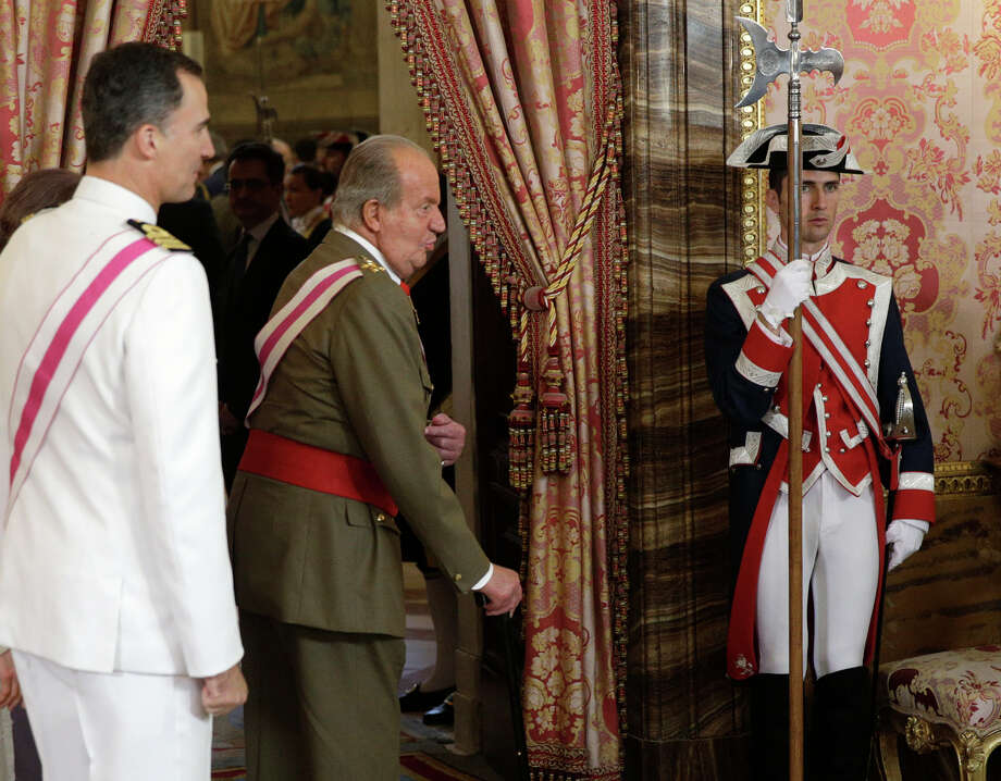 Spanish King Juan Carlos is followed by Spanish Crown Prince Felipe, left, as they attend a reception marking Spain's Armed Forces Day at the Royal palace in Madrid, Spain, Sunday, June 8, 2014.  King Juan Carlos plans to abdicate and pave the way for his son, Crown Prince Felipe, to become the country's next king. The 76-year-old Juan Carlos oversaw his country's transition from dictatorship to democracy but has had repeated health problems in recent years and his popularity dipped following royal scandals. Photo: Andrea Comas, AP / Pool Reuters