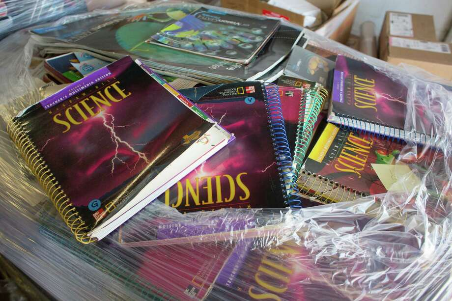 HISD is phasing out high school books, like these science texts at a school warehouse waiting to be recycled. The district is working to find a balance between electronic and physical learning materials. Photo: Johnny Hanson / © 2014  Houston Chronicle