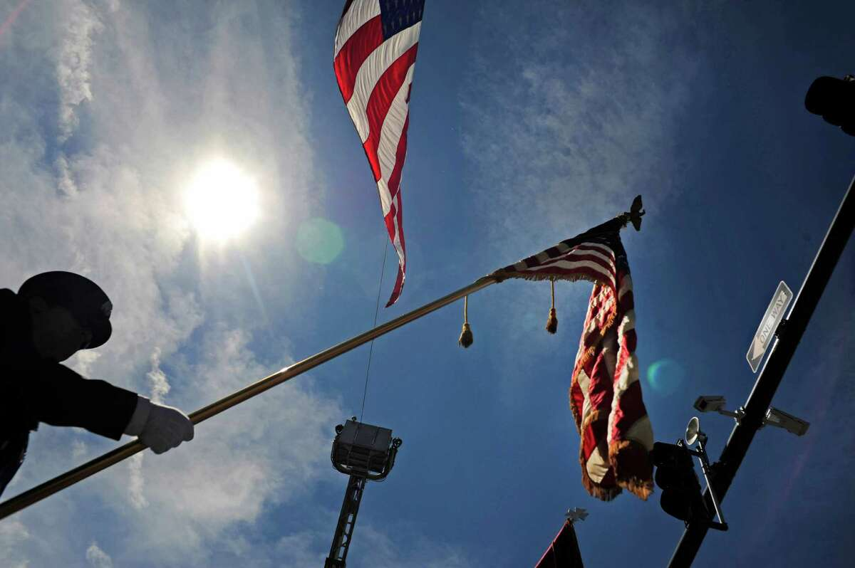 A member of the Speigletown Fire Department color guard marches down Fourth St. under a large American Flag in the 47th Annual Troy Flag Day Parade on Sunday, June 8, 2014, in Troy, N.Y. (Paul Buckowski / Times Union)