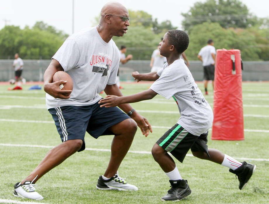 Justin Jones, 12, tries to wrap up Hall of Fame football player Eric Dickerson during the second day of the fifth annual Judson Football Camp at Rutledge Stadium Photo: Marvin Pfeiffer / San Antonio Express-News / Express-News 2014