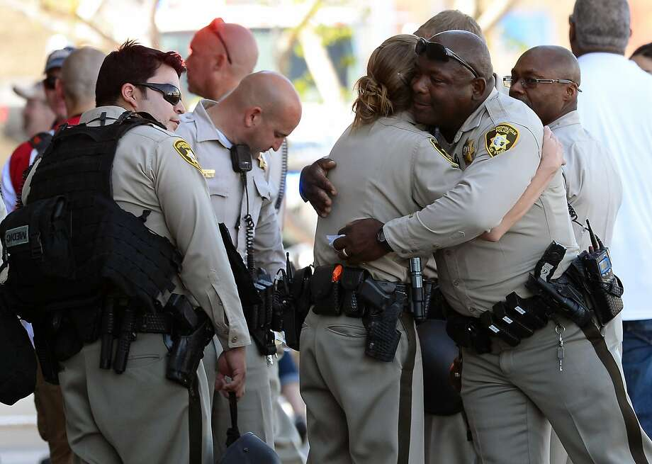 Las Vegas Metropolitan Police Department officers console each other after two assailants shot and killed two officers and a third person, then themselves. Photo: Ethan Miller, Getty Images