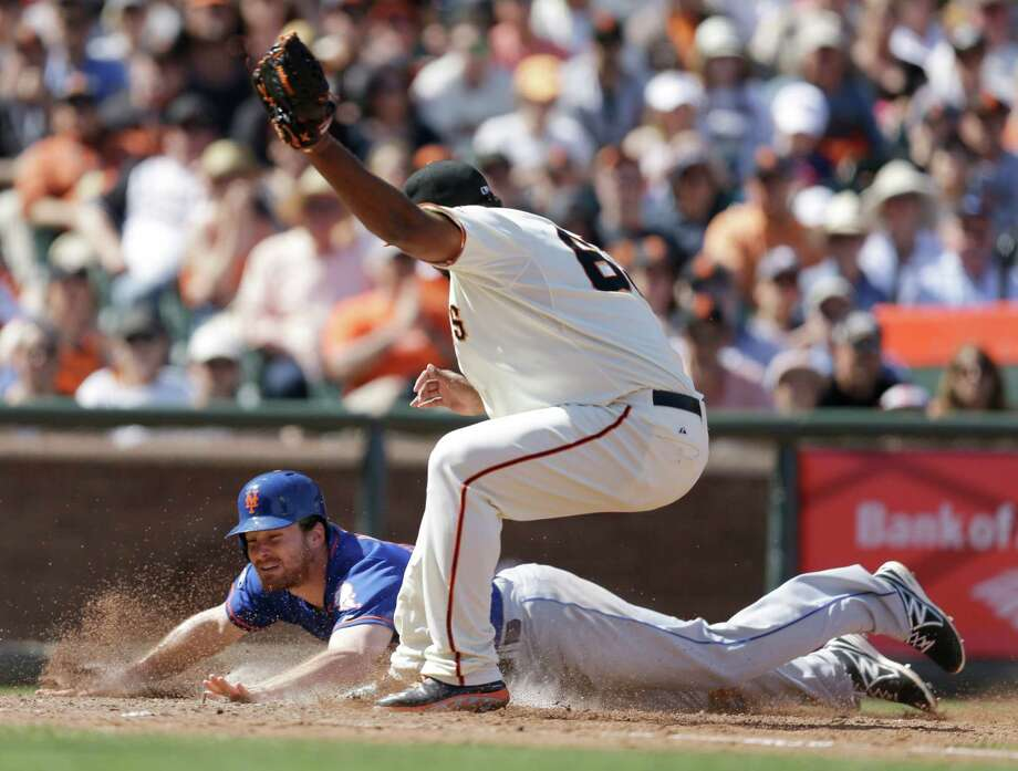 New York Mets' Daniel Murphy slides to score beneath San Francisco Giants pitcher Jean Machi in the eighth inning of a baseball game Sunday, June 8, 2014, in San Francisco. Murphy scored on a wild pitch from Machi. (AP Photo/Ben Margot) ORG XMIT: FXPB109 Photo: Ben Margot / AP