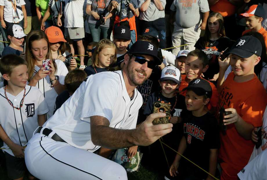 Detroit Tigers starting pitcher Justin Verlander takes a selfie with a group of kids during photo day at Comerica Park before a baseball game against the Boston Red Sox in Detroit, Sunday, June 8, 2014. (AP Photo/Carlos Osorio)  ORG XMIT: MICO104 Photo: Carlos Osorio / AP