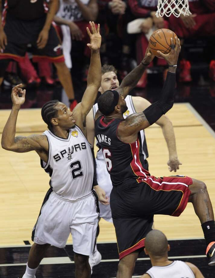 LeBron James, right, shoots against Kawhi Leonard, left, and Tiago Splitter during Game 2. Photo: Al Diaz, McClatchy-Tribune News Service
