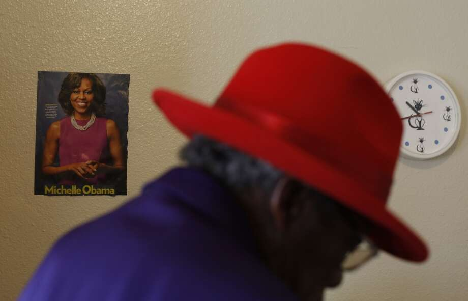Proud to have a wall to decorate at the Raman Hotel, Claude Holman stands next to a picture of Michelle Obama in San Francisco, Calif. Photo: Mike Kepka, The Chronicle