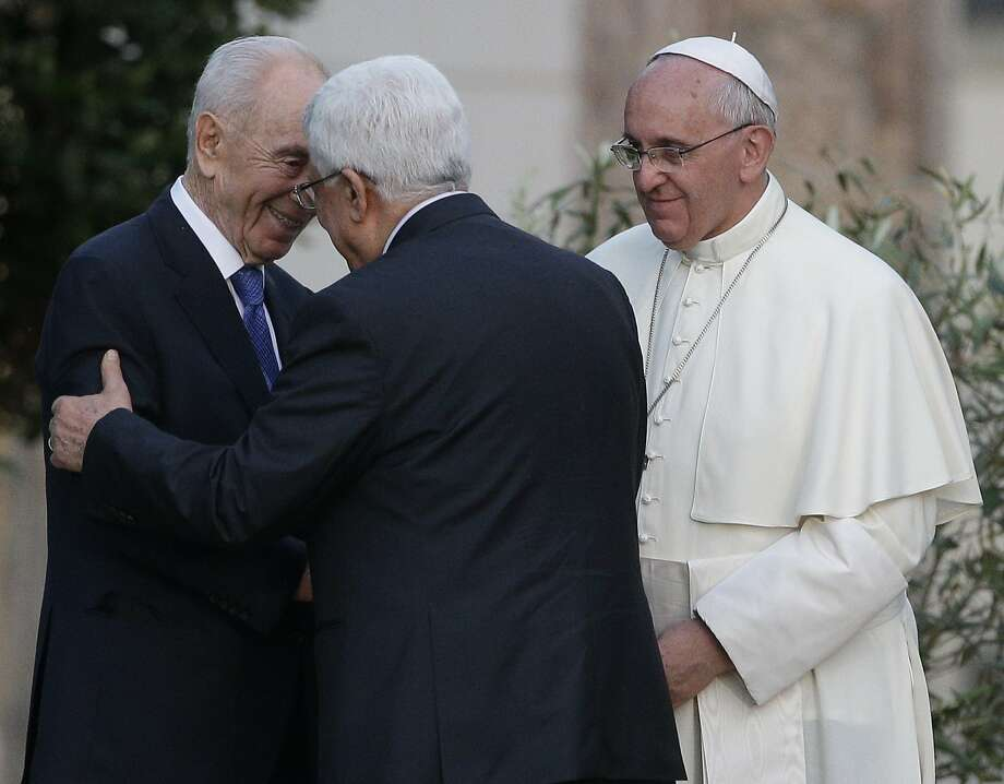 Pope Francis looks at Israel's President Shimon Peres, left, and Palestinian President Mahmoud Abbas embrace each other during an evening of peace prayers in the Vatican gardens, Sunday, June 8, 2014. Pope Francis waded head-first into Mideast peace-making Sunday, welcoming the Israeli and Palestinian presidents to the Vatican for an evening of peace prayers just weeks after the last round of U.S.-sponsored negotiations collapsed. (AP Photo/Gregorio Borgia) Photo: Gregorio Borgia, Associated Press