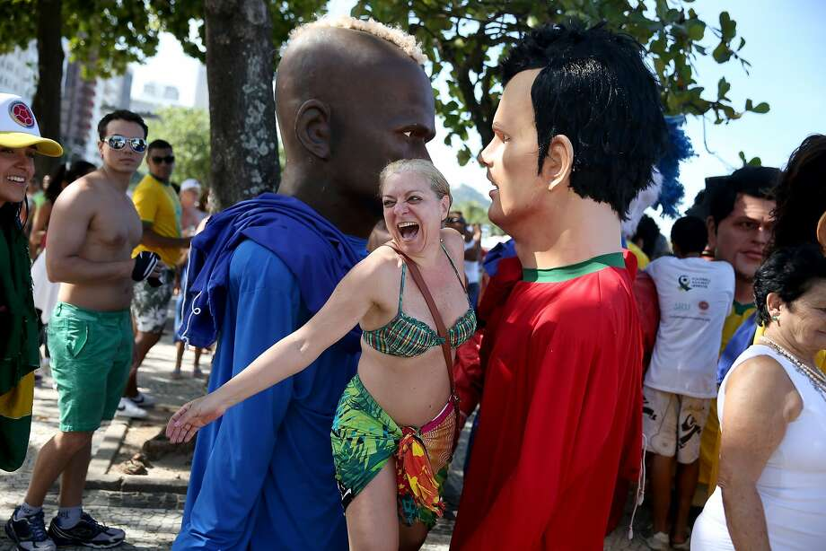 Mello in the middle: A laughing Cintya Mello inserts herself between giant World Cup star characters during the anti-hepatitis parade in Rio. Photo: Joe Raedle, Getty Images