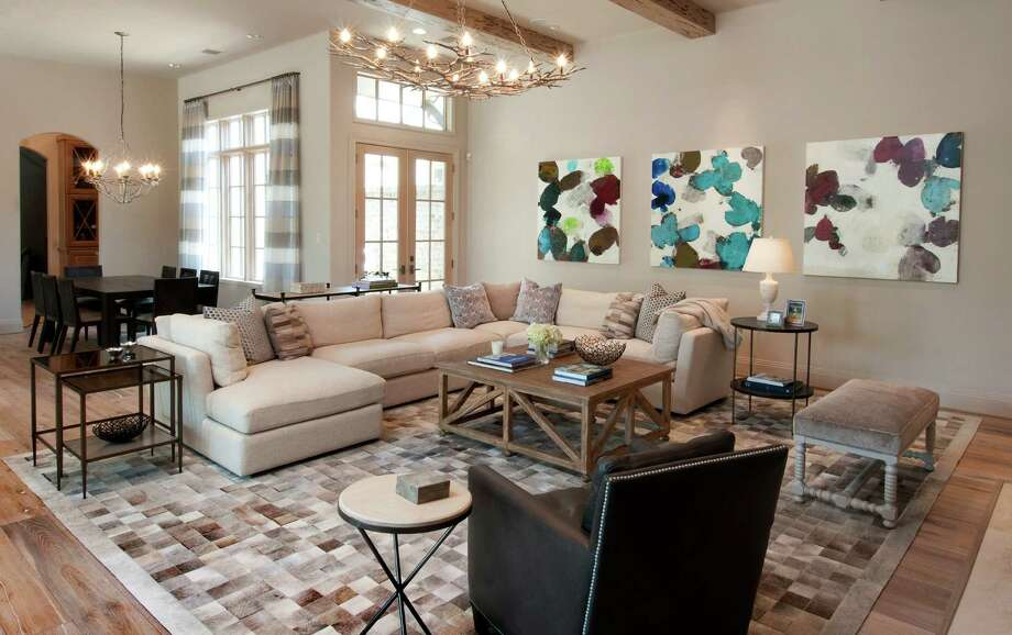 The family room at the Aquino home in The Woodlands gets a pop of color from an abstract triptych by Meredith Pardue found at Laura Rathe Fine Art in Houston, while the rug integrates all the different neutral tones found throughout the house. Photo: Don Glentzer / ONLINE_YES