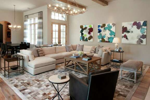 The family room at the Aquino home in The Woodlands gets a pop of color from an abstract triptych by Meredith Pardue found at Laura Rathe Fine Art in Houston, while the rug integrates all the different neutral tones found throughout the house.