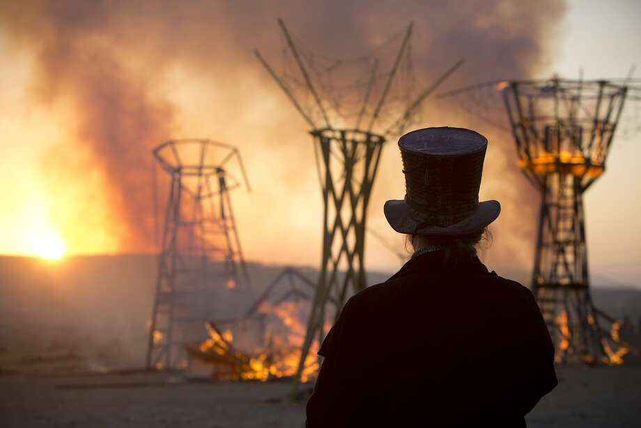 In this Saturday, June 7, 2014, photo, a man looks at a wooden sculpture that was set on fire during Israel's first Midburn Festival, modeled after the popular Burning Man Festival held annually in Nevada's Black Rock Desert, near the Israeli kibbutz of Sde Boker. Some 3,000 people set up a colorful encampment in the dusty moonscape, swinging from hoops by day and burning giant wooden sculptures by night.  Photo: Oded Balilty, Associated Press