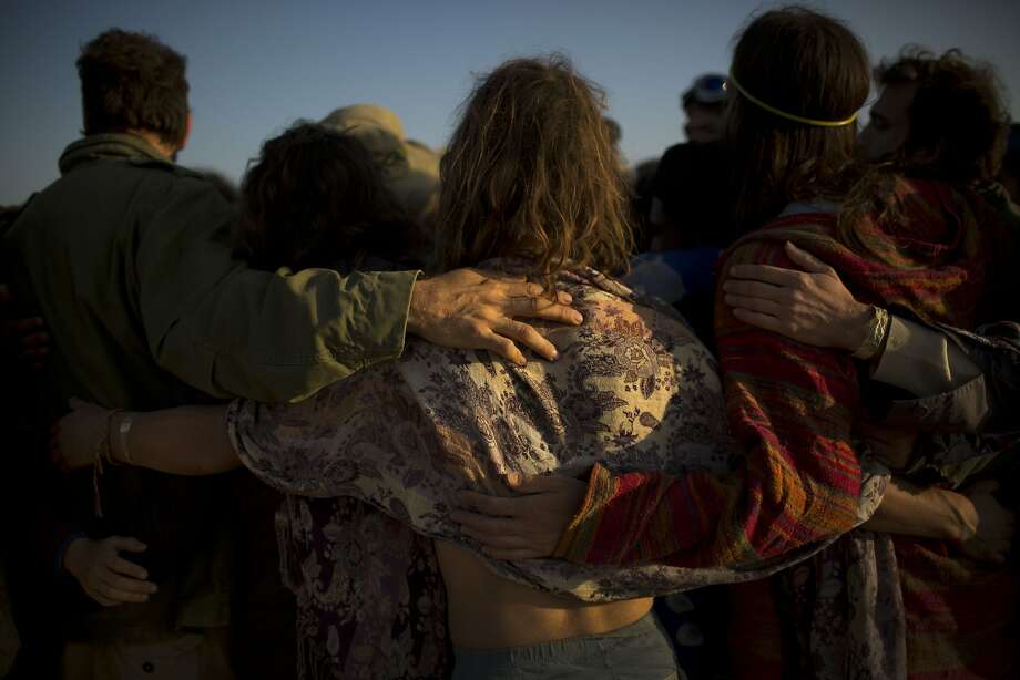 "In this photo taken Saturday, June 7, 2014, Israelis share a group hug after a wooden sculpture was set on fire during Israel's first Midburn festival, modeled after the popular Burning Man festival held annually in the Black Rock Desert of Nevada, in the desert near the Israeli kibbutz of Sde Boker. Some 3,000 people set up a colorful encampment in the dusty moonscape, swinging from hoops by day and burning giant wooden sculptures by night. For five days, participants mostly Israelis created a temporary city dedicated to creativity, communal living, and what the festival calls ""radical self-expression"". Photo: Oded Balilty, Associated Press"