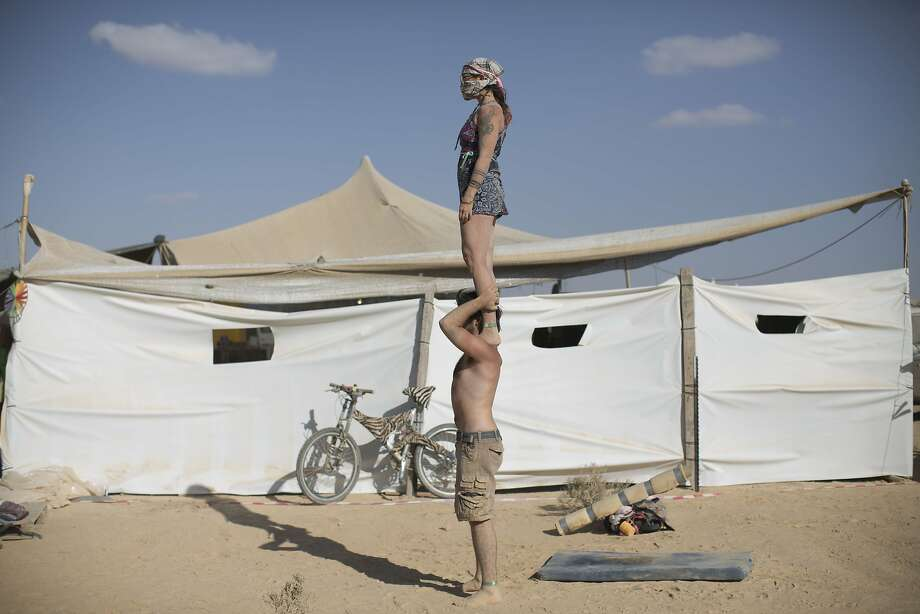 "In this photo taken Friday, June 6, 2014, Israeli acrobats perform during Israel's first Midburn festival, modeled after the popular Burning Man festival held annually in the Black Rock Desert of Nevada, in the desert near the Israeli kibbutz of Sde Boker. Some 3,000 people set up a colorful encampment in the dusty moonscape, swinging from hoops by day and burning giant wooden sculptures by night. For five days, participants mostly Israelis created a temporary city dedicated to creativity, communal living, and what the festival calls ""radical self-expression"". Photo: Oded Balilty, Associated Press"
