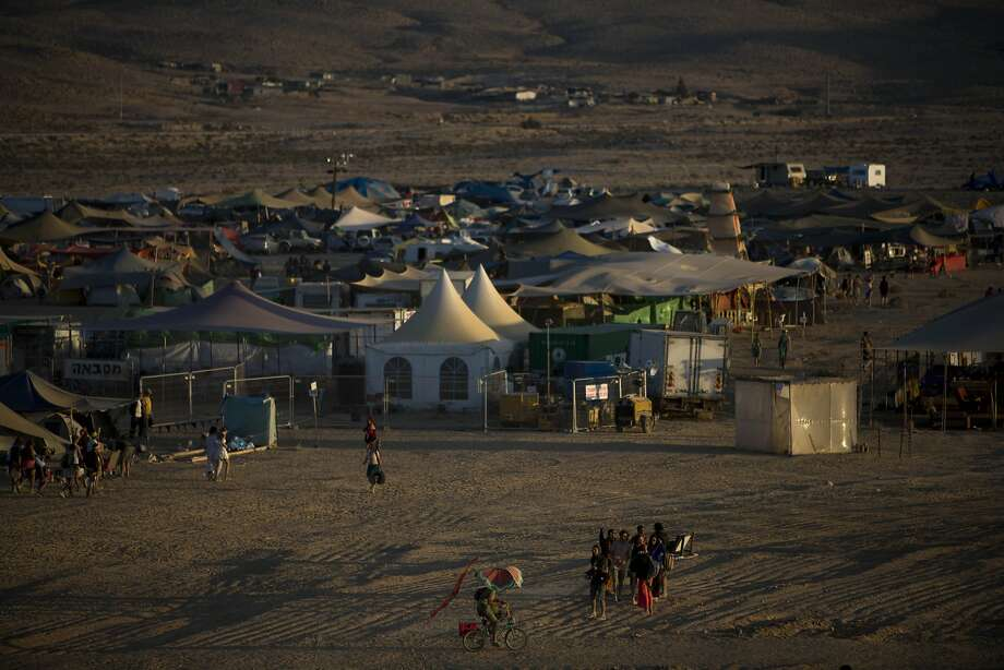 "This photo taken Friday, June 6, 2014, shows a general view of the playa during Israel's first Midburn festival, modeled after the popular Burning Man festival held annually in the Black Rock Desert of Nevada, in the desert near the Israeli kibbutz of Sde Boker. Some 3,000 people set up a colorful encampment in the dusty moonscape, swinging from hoops by day and burning giant wooden sculptures by night. For five days, participants mostly Israelis created a temporary city dedicated to creativity, communal living, and what the festival calls ""radical self-expression"".  Photo: Oded Balilty, Associated Press"