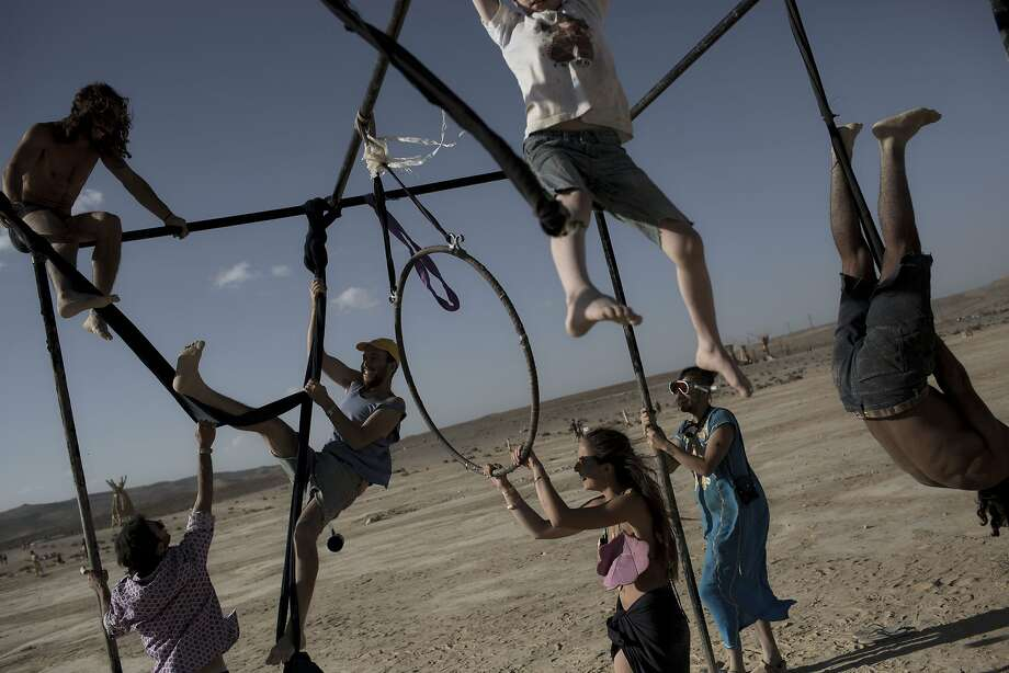 "In this photo taken Friday, June 6, 2014, Israelis climb on one of the art installation during Israel's first Midburn festival, modeled after the popular Burning Man festival held annually in the Black Rock Desert of Nevada, in the desert near the Israeli kibbutz of Sde Boker. Some 3,000 people set up a colorful encampment in the dusty moonscape, swinging from hoops by day and burning giant wooden sculptures by night. For five days, participants mostly Israelis created a temporary city dedicated to creativity, communal living, and what the festival calls ""radical self-expression"". Photo: Oded Balilty, Associated Press"