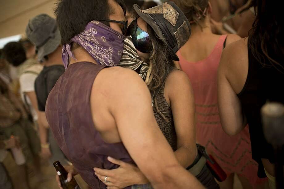 "In this photo taken Thursday, June 5, 2014, Israelis kiss at a party during Israel's first Midburn festival, modeled after the popular Burning Man festival held annually in the Black Rock Desert of Nevada, in the desert near the Israeli kibbutz of Sde Boker. Some 3,000 people set up a colorful encampment in the dusty moonscape, swinging from hoops by day and burning giant wooden sculptures by night. For five days, participants mostly Israelis created a temporary city dedicated to creativity, communal living, and what the festival calls ""radical self-expression"". Photo: Oded Balilty, Associated Press"