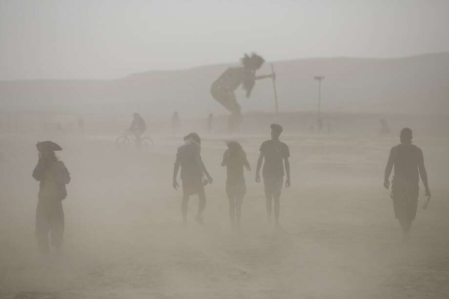 "In this photo taken Thursday, June 5, 2014, people walk in the dusty playa during Israel's first Midburn festival, modeled after the popular Burning Man festival held annually in the Black Rock Desert of Nevada, in the desert near the Israeli kibbutz of Sde Boker. For five days, participants, mostly Israelis, created a temporary city dedicated to creativity, communal living, and what the festival calls ""radical self-expression.""  Photo: Oded Balilty, Associated Press"