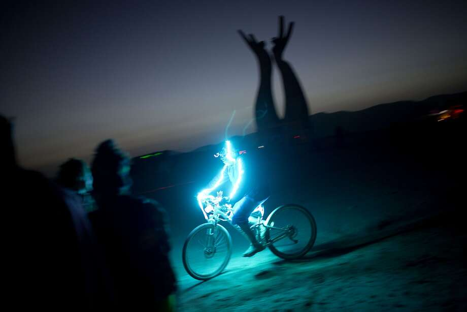 "In this photo taken Thursday, June 5, 2014, An Israeli man rides a bicycle as the sun goes down during Israel's first Midburn festival, modeled after the popular Burning Man festival held annually in the Black Rock Desert of Nevada, in the desert near the Israeli kibbutz of Sde Boker. For five days, participants _ mostly Israelis _ created a temporary city dedicated to creativity, communal living and what the festival calls ""radical self-expression.""  Photo: Oded Balilty, Associated Press"