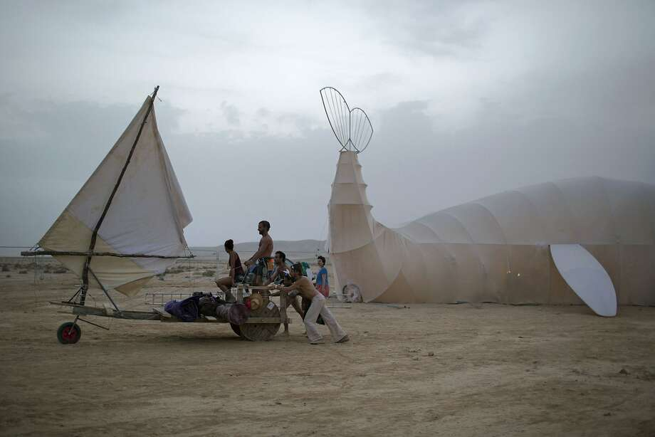 """In this photo taken Wednesday, June 4, 2014, Israelis push a sailboat art car at the playa during the Israel's first Midburn festival, modeled after the popular Burning Man festival held annually in the Black Rock Desert of Nevada, in the desert near the Israeli kibbutz of Sde Boker. Some 3,000 people set up a colorful encampment in the dusty moonscape, swinging from hoops by day and burning giant wooden sculptures by night. For five days, participants mostly Israelis created a temporary city dedicated to creativity, communal living, and what the festival calls """"radical self-expression."""" Photo: Oded Balilty, Associated Press"""