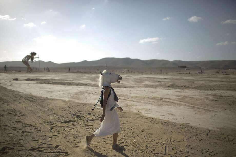 "In this photo taken Friday, June 6, 2014, An Israeli woman wears a unicorn mask as she walks in the playa during Israel's first Midburn festival, modeled after the popular Burning Man festival held annually in the Black Rock Desert of Nevada, in the desert near the Israeli kibbutz of Sde Boker. Some 3,000 people set up a colorful encampment in the dusty moonscape, swinging from hoops by day and burning giant wooden sculptures by night. For five days, participants mostly Israelis created a temporary city dedicated to creativity, communal living, and what the festival calls ""radical self-expression."" Photo: Oded Balilty, Associated Press"