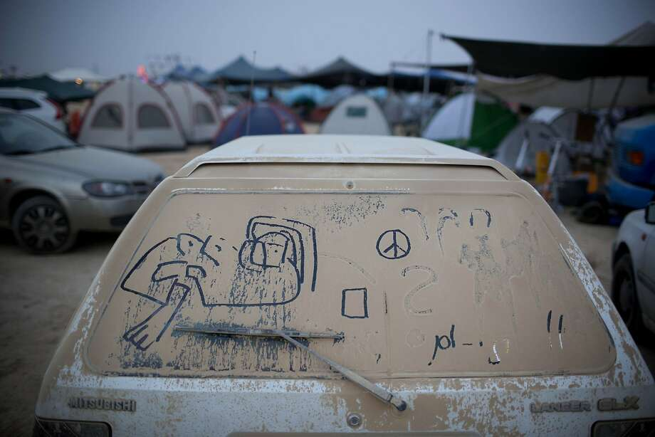 "In this photo taken Wednesday, June 4, 2014, hand writing and doodles adorn a dusty car during Israel's first Midburn festival, modeled after the popular Burning Man festival held annually in the Black Rock Desert of Nevada, in the desert near the Israeli kibbutz of Sde Boker. For five days, participants _ mostly Israelis _ created a temporary city dedicated to creativity, communal living and what the festival calls ""radical self-expression.""  Photo: Oded Balilty, Associated Press"