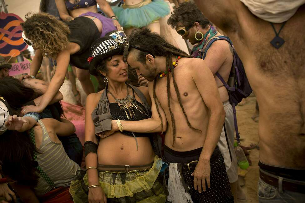 In this photo taken Thursday, June 5, 2014, Israelis dance at a party during Israel's first Midburn festival, modeled after the popular Burning Man festival held annually in the Black Rock Desert of Nevada, in the desert near the Israeli kibbutz of Sde Boker. Some came costumed in cape or corset. Others, from babies to grandparents, went nude. Participants brought their own food and water, and shared with others. The only thing on sale was ice because of the scorching heat. There were workshops in sculpture, drawing, and touch therapy. There was music and theater. At the